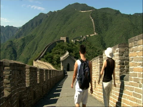 view along great wall of china, two tourists walk away from camera, mutianyu, china - mutianyu stock videos & royalty-free footage