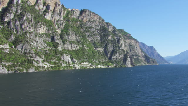 WS AERIAL View along lake and mountain / Lake Garda, Trentino, Verona, Brescia