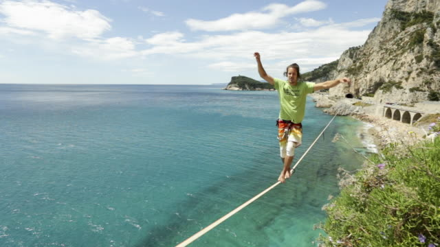 view along line to athlete traversing highline above sea - acrobata video stock e b–roll