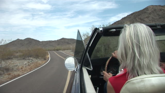 MS view along side of convertible as woman drives down desert road/ Scottsdale, Arizona