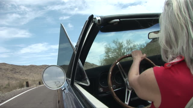 ms view along side of convertible as woman drives down desert road/ scottsdale, arizona - gray hair stock videos and b-roll footage