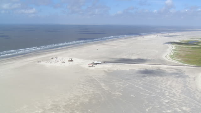 ws aerial view approach to coastline and beach chairs / sankt pete ording, schleswig holstein - north sea stock videos & royalty-free footage