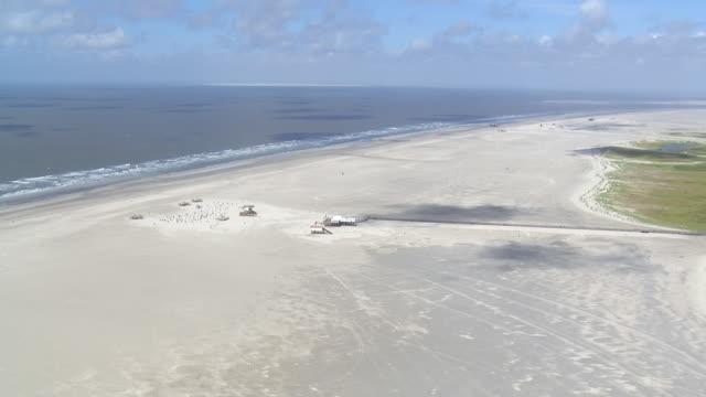 ws aerial view approach to coastline and beach chairs / sankt pete ording, schleswig holstein - deutsche nordseeregion stock-videos und b-roll-filmmaterial