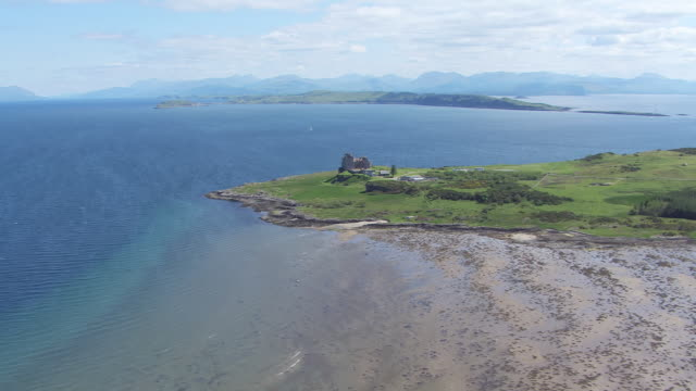 vidéos et rushes de ws aerial view approaching duart castle with mainland and loch linnhe beyond / isle or island of mull, argyll and bute, scotland - mull