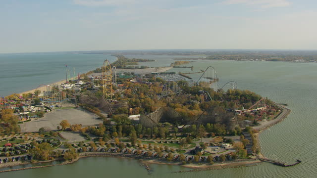 ws td aerial view approaching over cedar point amusement park on lake erie peninsula / sandusky, ohio, united states - ohio stock videos & royalty-free footage