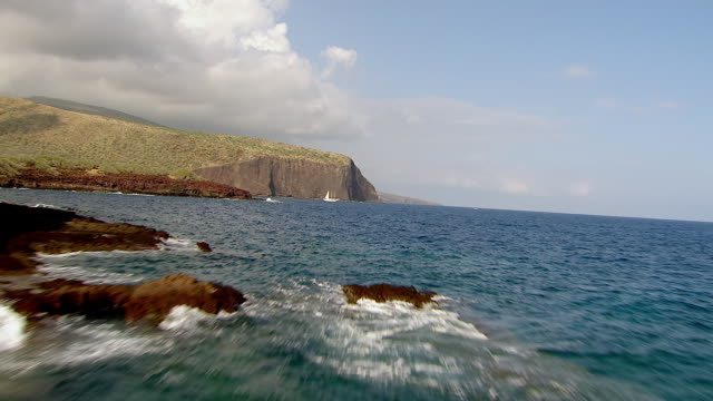 WS AERIAL View approaching through rocks over sailboat near island of Lanai / Hawaii, United States