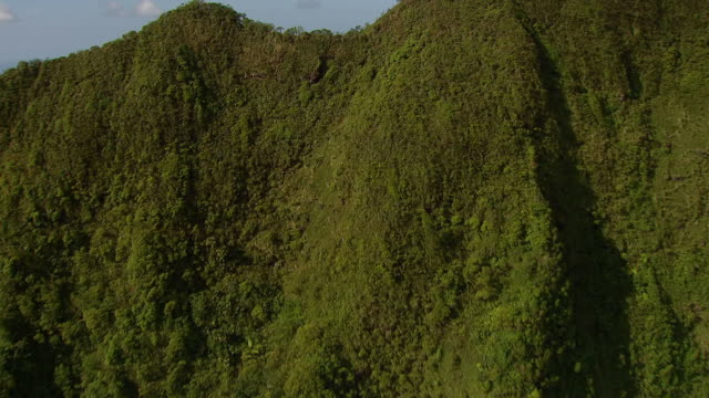 ws aerial view approaching to large green mountains to downtown waikiki on island of oahu / honolulu, hawaii, united states - honolulu stock videos and b-roll footage