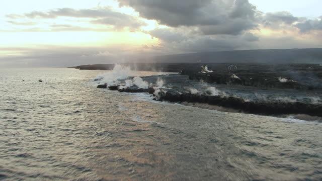 WS AERIAL View approaching to lava smoking from Volcano Kilauea near coastline on big island / Hawaii, United States