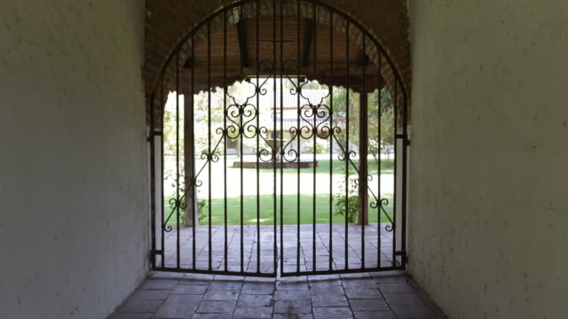 view at a hand crafted steel gate at a jesuit house in calera de tango chile through the gate's poles the backyard of the house is visible there is a... - metal blend stock videos and b-roll footage