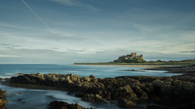 A view at dusk across the rocks and beach looking towards Bamburgh Castle on the coastal shores of the North Sea