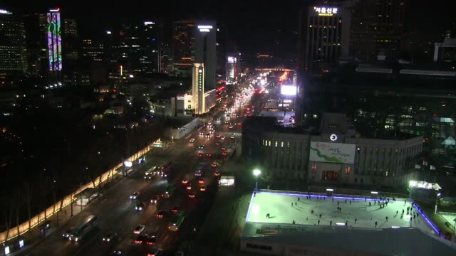 view at night of people skating on large outdoor ice rink located in seoul plaza and traffic running through sejong-daero avenue in jongno district.... - eddie large stock videos & royalty-free footage