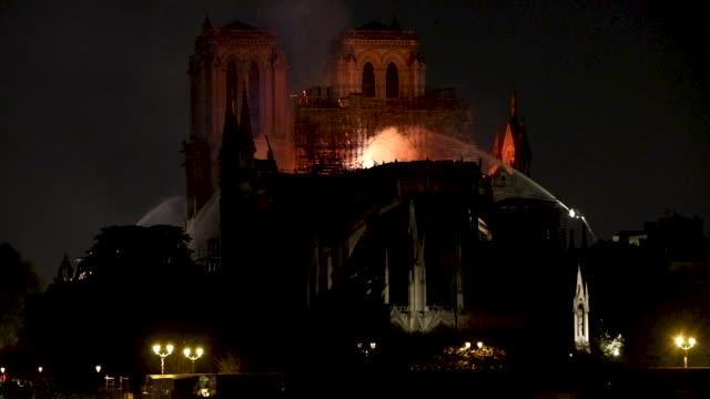 view at the notre-dame cathedral from the pont de la tournelle on april 15, 2019 in paris, france. a fire broke out on monday afternoon and quickly... - notre dame de paris stock videos & royalty-free footage