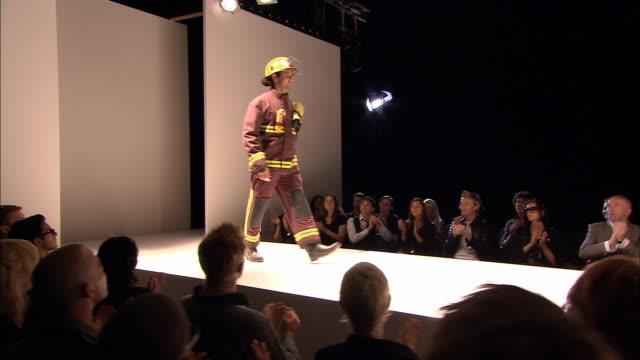 ms view behind audience as model dressed as fireman walks onto catwalk at fashion show/ tu pan man walking down catwalk, turning around, and walking back/ london, england - この撮影のクリップをもっと見る 1064点の映像素材/bロール