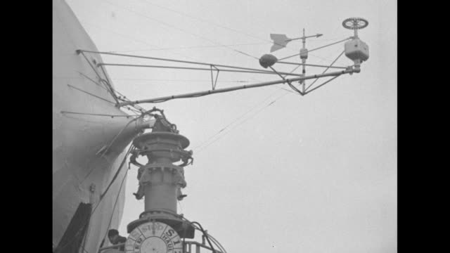 View beneath the US Navy rigid airship showing the gondola and large motors at right / an array of scientific instruments including a weather vane...