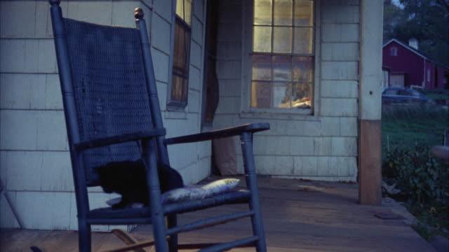 vídeos y material grabado en eventos de stock de ms view black cat sitting on rocking chair in porch - pórtico