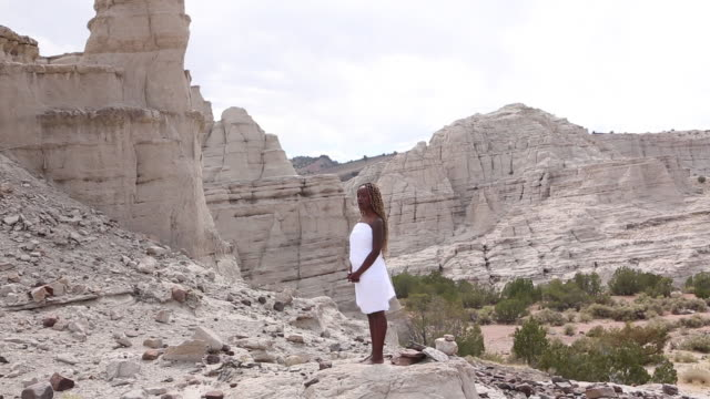 vidéos et rushes de ws pan view black woman in desert / santa fe, new mexico, united states - robe