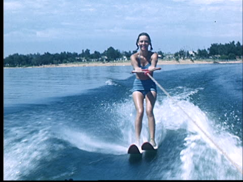 rear pov, view boat at young woman water skiing on lake, 1950's, oklahoma, usa - bikini stock videos & royalty-free footage