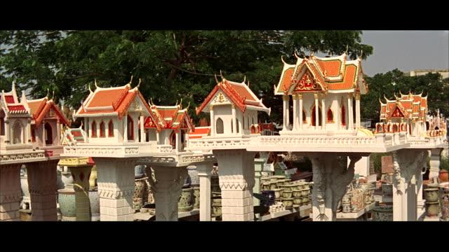 vídeos de stock, filmes e b-roll de ms view  buddhist temple joss houses small buildings containing idols - formato letterbox
