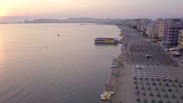 view by drone of beach at sunset, durres (epidamnos) (dyrrachium), adriatic coast, albania, europe - albania stock videos & royalty-free footage