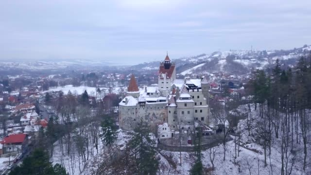 view by drone of bran castle covered in snow in winter, transylvania, romania, europe - romania stock videos & royalty-free footage