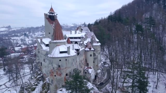 view by drone of bran castle covered in snow in winter, transylvania, romania, europe - transilvania video stock e b–roll