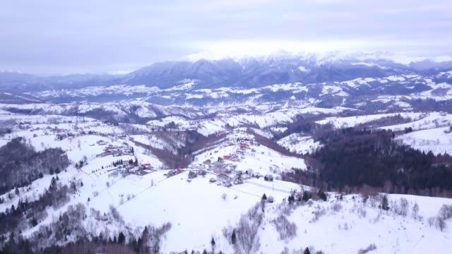 view by drone of snowy winter landscape in the carpathian mountains near bran castle, transylvania, romania, europe - transylvania stock videos & royalty-free footage