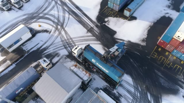MS View crane lifting cargo container in snowy shipyard
