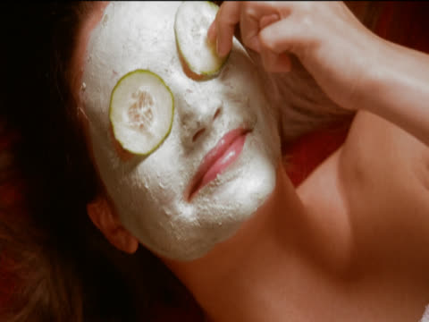 view directly above of a woman lying down wearing a face mask, taking cucumber slices from her eyes and laughing - cucumber stock videos and b-roll footage