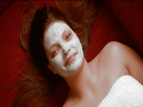 view directly above of a woman lying on the floor, wrapped in a towel and wearing a face mask, taking cucumber slices from her eyes and laughing - wrapped in a towel stock videos & royalty-free footage