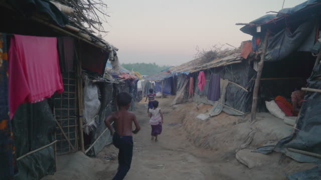 View down alleyway as children run past in Kutupalong refugee camp in Bangladesh Children make up over 50% of those in the camps and when walking...