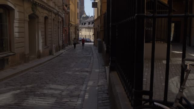 view down narrow street towards riddarholmen church, gamla stan, stockholm, sweden, scandinavia, europe - etwa 13. jahrhundert stock-videos und b-roll-filmmaterial