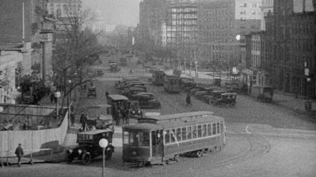 View down Pennsylvania Ave man riding bicycle / trolley and cars on streets in Washington DC 1921