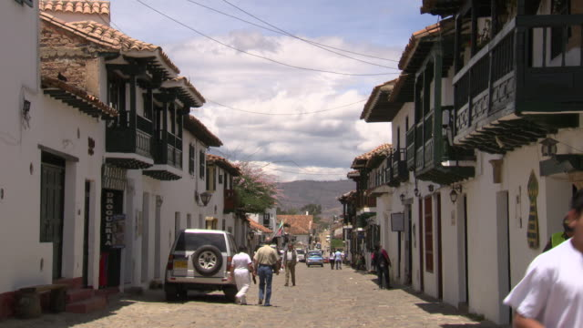 vídeos de stock e filmes b-roll de view down residential street with people and cars, white houses and red tiled roofs,  villa de leyva, boyacã¡ department, colombia - colômbia
