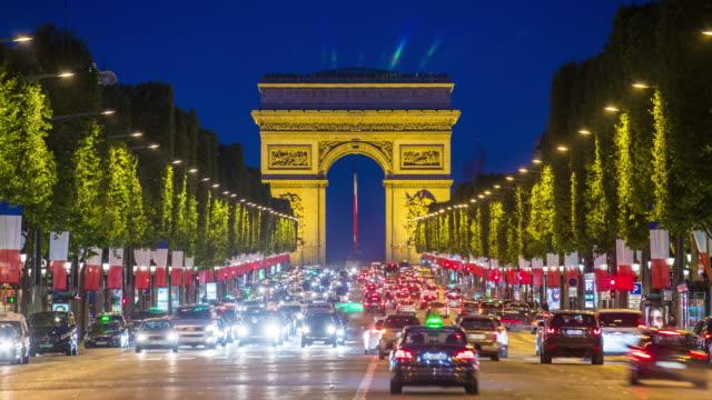 vidéos et rushes de view down the champs elysees to the arc de triomphe, illuminated at dusk, paris, france - time lapse - arc élément architectural