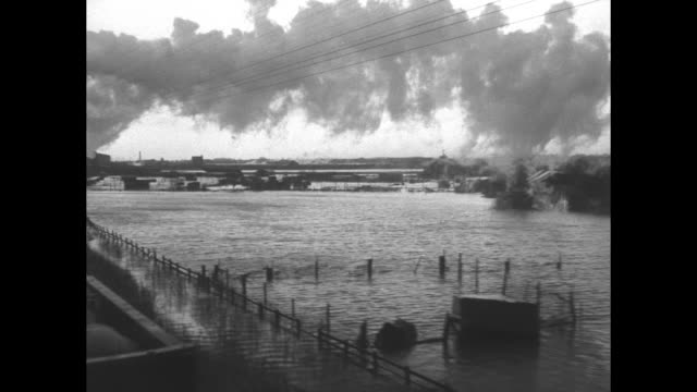 View flooded countryside across train car loaded with sandbags steam engine smoking ahead on Canvey Island England / VS flooded tracks / rows of...