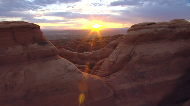 WS AERIAL View flying over bluffs to sunrise in between rock formations at arches national park / Utah, United States