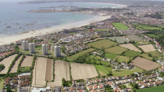 ws aerial view flying over city and beach / guernsey, channel isles - guernsey stock-videos und b-roll-filmmaterial