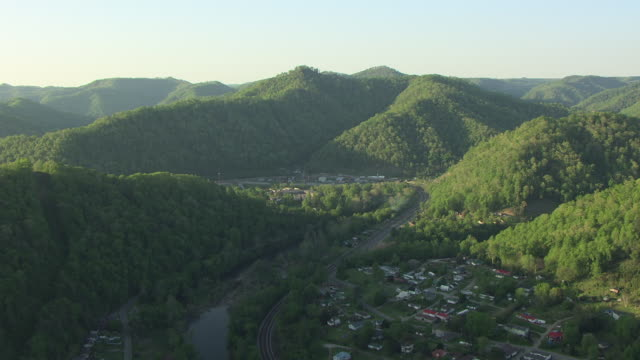 ws aerial view flying over hills to reveal town / mccarr, kentucky, united states - ケンタッキー州点の映像素材/bロール