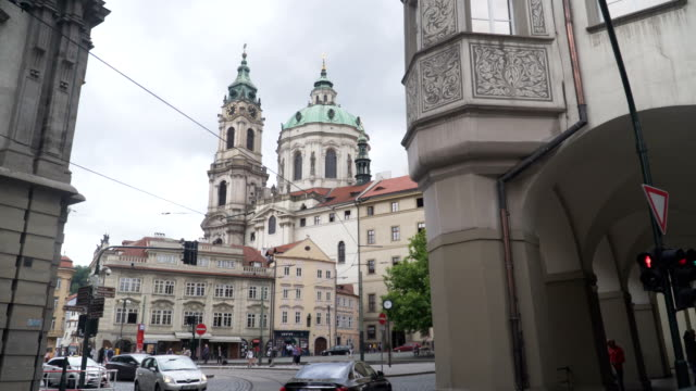 view form traveller see the church of saint nicholas in the old town of prague. - mala strana stock videos and b-roll footage