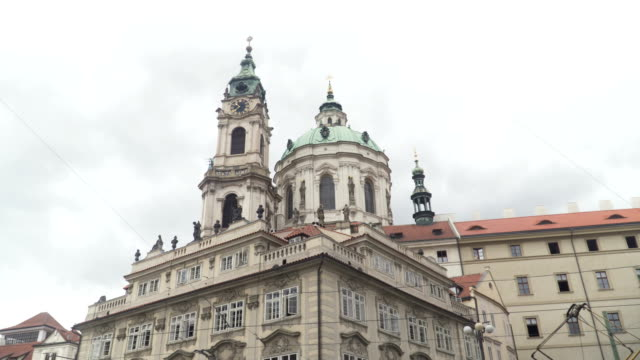 view form traveller walking to see the church of saint nicholas in the old town of prague. - mala strana stock videos and b-roll footage