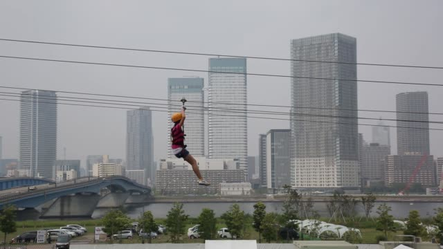 A view from a car driving through the central business district of Tokyo Japan on Monday Aug 12 Children glide on a zip line past high rise buildings...