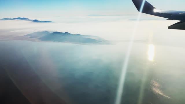 大規模な水域を飛行中の翼の民間旅客機ジェット乗客の窓からの眺めと、部分的に曇りで晴れた日の島 - sunny点の映像素材/bロール
