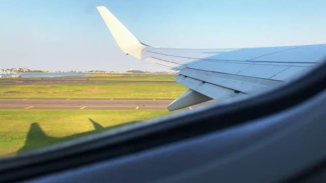 blick von einem kommerziellen fluggast-fenster der flüster-und umgebenden flat-landschaft während der fahrt von einem flughafen auf einem klaren morgen - abheben aktivität stock-videos und b-roll-filmmaterial