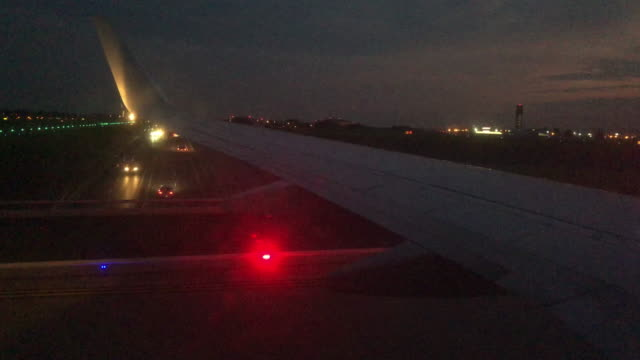 view from a commercial airliner jet passenger window of the wing while taxiing down an airport runway at dusk - taxiing stock videos & royalty-free footage