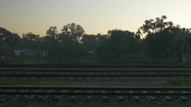 View from a diesel passenger train with packed carriages crossing Northern Bangladesh at dawn