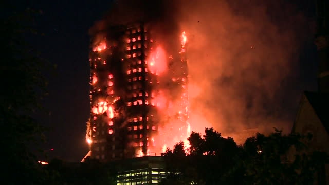 view from a distance of the grenfell tower engulfed by fire at night - bbc点の映像素材/bロール