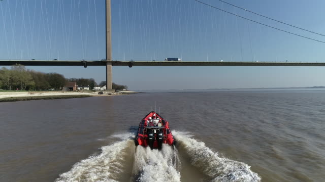 view from a drone following a lifeboat as it passes underneath the humber bridge - rescue worker stock videos & royalty-free footage