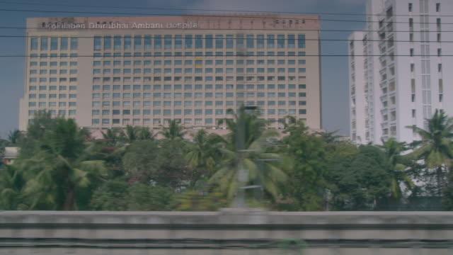 POV view from a monorail train of buildings including Kokilaben Dhirubhai Ambani Hospital Mumbai Maharashtra India FKAD675A Clip taken from programme...