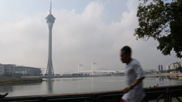 view from a moving car of the macau tower convention entertainment centre and the hong kongzhuhaimacao bridge main bridge - main tower stock-videos und b-roll-filmmaterial