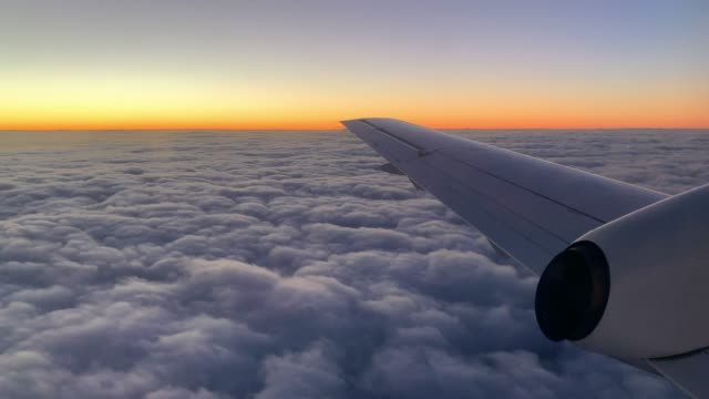 view from a plane above the clouds at sunset - commercial aircraft stock videos & royalty-free footage
